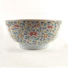 An 18th century Chinese export porcelain punch bowl. An 18th century Chinese export porcelain punch bowl. Qianlong period (1736 - 1795). Of circular form, the exterior overglaze painted in enamels depicting a group of scholars enclosed within a gilt cartouche and profusely decorated with a colourful array of flowers, the interior edge decorated with a gilt and iron red foliate pattern border. 10.3 in (26.2 cm) diameter.