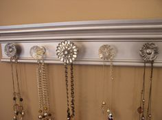 jewelry/necklace organizer holder wall hung rack with 5 knobs on silver metallic finished 15 inches long. $28.50, via Etsy.