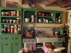 ...Com um jeito rústico.   Eu fiz os armários, a mesa, o nicho do fogão e os quadros.   O revestimento 'azulejado' também feito por mim.   ...