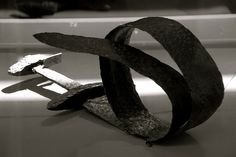 The sword has been heated and bent by a blacksmith before the owner's funeral. Swords could have names and some were treated as individuals. The bending could be seen as the symbolic death of the sword.