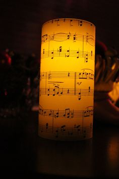 Sheet music wrapped around battery operated candle.  Could secure with double sided tape.
