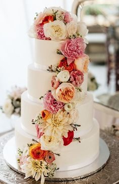 Elegant four tier white wedding cake decorated by gorgeous flowers; Featured Photographer: Joel Bedford
