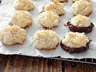 Treat your guests with these delicious coconut macaroons that baked using almond extract and dipped in melted chocolate – a tropical treat.