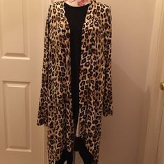 NEWBrown Leopard Print Long Duster I never met an animal print I didn't love! And this long duster is no exception. Rayon with 3% spandex makes for a comfy fit while maintaining its shape. Wear with a cami and leggings and your good to go for any occasion!  This piece is from Chicos and is a size 3 which converts to an XL. Hem has beautiful brown velvet type border. Chicos Tops Tunics