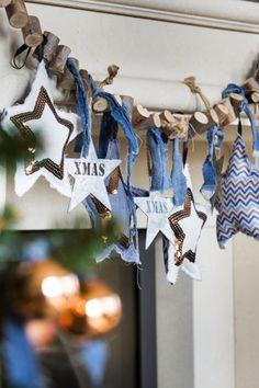 Kerststijl Urban Mountain - Maak een stoere guirlande voor aan de schouw of in de kerstboom. Pak als basis een stoere houten slinger en hang daar met repen spijkerstof verschillende decoratieve elementen aan. Eens helemaal anders!