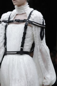 Strapped in... soft, fluffy white ruffles with contrasting black belt detail - interesting juxtapositions in fashion design // Alexander McQueen