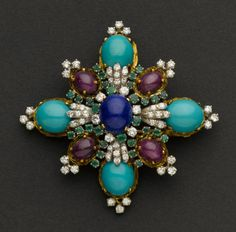 Exceptional Diamond, Emerald, Ruby, Lapis & Turquoise Pendant/Brooch By J.G.Jlry (Jack Gutschneider, NYC), circa 1960's measures 60 mm across, 18k gold, centered by a 12 x 10 mm lapis lazuli cabochon, round diamonds and emeralds, four ruby cabochons, four large Persian turquoise cabochons, with pin back and a bale, 27.4 grams, signed on the back center bar