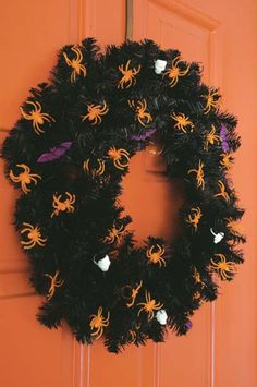 All you need is a cheap Christmas wreath, a can of black spray paint, a glue gun and a $1.00 bag of plastic Halloween trinkets. (Of course, the orange door helps, too!  LOL)