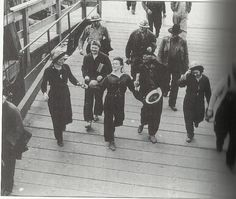 men and women leaving work during WWII