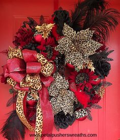 "Leopard Christmas Wreath for front door ""Exotic Holiday"" Designer Christmas Wreath IS NOW ON SALE!! WOW! Designer handcrafted Christmas wreath filled with gorgeous leopard print poinsettias, beautiful artificial flowers, glittering stems, leopard ornaments and ribbon, and lovely black ostrich feathers. This uniquely designed Christmas wreath measures approx: 30"". (Wreath measures approx: 37"" from feather tip to feather tip.) FREE US SHIPPING!"