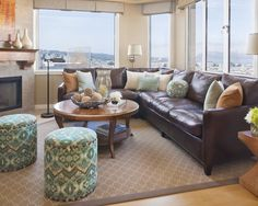 Decorate around brown furniture: The pillows tie the room together ~ they pick up wall color, lamp shades, accessories, art, ottomans, table, and window treatments; dark vanilla rug w/ dark binding and light graphic pattern adds another layer of pattern and texture; upholstered ottomans introduce a more complex pattern as well as fresh green, AND the view is not blocked!