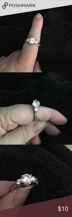 CZ 3 stone Silver tone engagement ring Center larger stone looks like it could be 1 1/2 -2 CT in size White CZ. Two side stone rack look like about 1/4  white CT CZ.   Size 9 . Also there is detail work around outside of either side of the ring. Quite pretty. Jewelry Rings