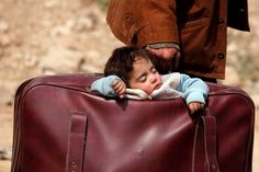 A child sleeps in a bag as hundreds of civilians leave rebel-held Eastern Ghouta, Syria. (Omar Sanadiki / Reuters) https://pow.photos/2018/international-pow-12-19-march/