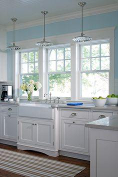 Glass pendant lighting, white farm sink, kitchen windows, white cabinets, light blue walls    Signature Kitchens