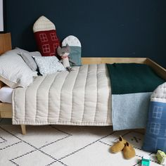 Single bed hand quilted blanket, house cushions and knitted merino wool blanket all by Camomile london
