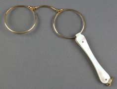 Lot 710, A pair of gilt pince nez with mother of pearl handle, est £50-100