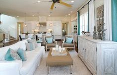 Open concept living room features white slipcovered sofa with ruffled skirt accented with turquoise and blue pillows paired with burlap bench with fringe trim and Oly Studio Hanna Lounge Chairs upholstered in taupe fabric with turquoise blue pillows. Living Room Ceiling Fan, Beach Living Room, Cottage Living Rooms, Coastal Living Rooms, Home Living Room, House Of Turquoise, Luxury Interior Design, Luxury Homes, Turquoise Pillows