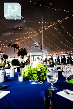 wedding reception under a tent with string lights and blue and green colors.