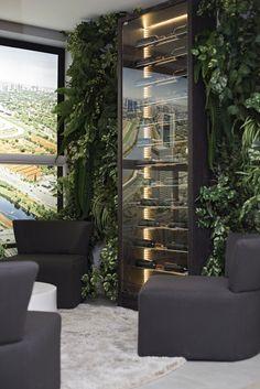 """Um terraço bem aconchegante, onde a adega fica emoldurada recebe uma """"moldura""""verde. Espécies diversificadas compõem esses painéis!"""