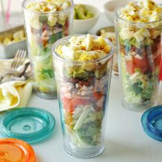 A simple and delicious cobb salad layered into to-go drinking tumblers. It's a great tip to repurpose those cups you have laying around!