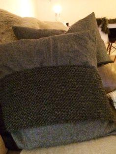 Stickad detalj mot filttyg som veckar sig vid sömnad. Vacker i sin enkelhet.