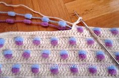 """Beautiful baby blanket, made with wool pompom, with step by step images, blogger found on the site """"Marifetane.com"""". All white wool interwoven with 2 colours of pompom yarn, surrounded by a pretty lace border. Possible to use idea with other work, such as bags, wallets, etc"""