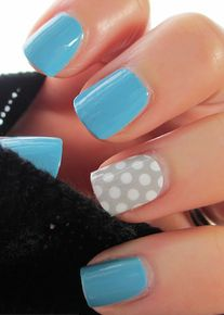 Simple pale blue nails and a gray and white polka dotted feature nail