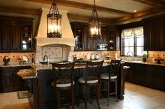 Dark wood kitchen, floating with bulky crown molding.  Light and large stove hood