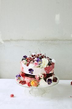 white layer cake with colorful berries + flowers