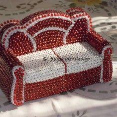 Miniatur Sofa, eine bezaubernde Dekoration auf dem Schränkchen, in der Vitrine, auf der Fensterbank oder in einer großen Puppenstube. Die Miniatur Couch ist ein toller Eyecatcher und wird alle Blicke auf sich ziehen. Diese wunderschöne und einzigartige Couch wurde von mir in liebevoller Handarbeit  nach eigenen Ideen gestaltet.Ich habe rote hologramm-irisierende und weiße Metallic-Pailletten in einem wunderschönen Design kombiniert mit Perlkopfnadeln gesteckt. Die Rückseite und Stellfläche…