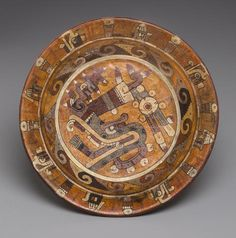 Aztec, Eastern Nahua, Polychrome Tripod Plate, ca. A.D. 1300-1521 Earthenware with polychrome paint height 4 1/4in (10.8cm)  Finely painted with fire serpent head and feather motifs.