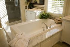 There is nothing more relaxing than a giant soaking tub! We love how this room surrounds the tub with a white marble and sits a window at the foot of it. Find 26 Bathrooms with Striking White Cabinets at http://www.homestratosphere.com/bathrooms-white-cabinets/#utm_sguid=163048,7291fb4a-5550-cd82-f154-e2a1a9920715 See 100s more bathroom designs at http://www.homestratosphere.com/category/bathrooms/#utm_sguid=163048,7291fb4a-5550-cd82-f154-e2a1a9920715