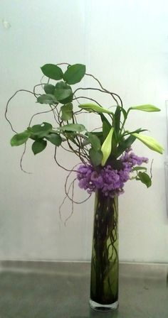 Purple statis collar, twisted willow and closed casablanca lilies.