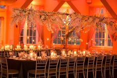Uplighting is a budget-friendly way to immediately transform a room's ambiance. An orange glow bathes this reception in a romantic light.