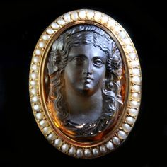 Oval cameo brooch with a large central citrine carved in high relief representing a classical bust with a yellow gold and split-pearl border French circa 1890