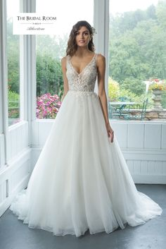Feel romantic and beautiful in this ball gown. The illusion V-neckline on front and back is accented with lattice beaded lace. Complete the look with a tulle circular cut skirt with a chapel length train.