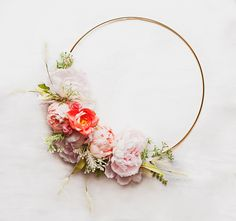This wreath is part of the Adore series and features soft, blush peonies with coral and light pink accents, atop delicate berries and light greenery on a gold hoop. It is whimsical, and would be beautiful in nursery or as a chic decorative piece! This item is one of a kind, and is the item as-sh