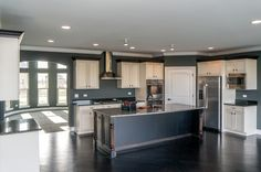 Large chef inspired kitchen with two tone cabinet finish. Painted white surrounding cabinets and dark stained center island with granite countertops. Two Tone Cabinets, Maple Cabinets, Custom Kitchen Cabinets, Old World Style, Granite Countertops, Amelia, Luxury Homes, Building A House, House Plans