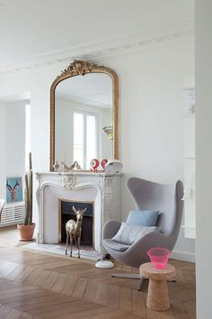 A renovated Paris flat - French By Design. Get the look with similar products from Schots Home Emporium https://www.schots.com.au/fireplaces/marble-mantles/louis-xv-chateau-mantle.html https://www.schots.com.au/domed-overmantle-mirror.html  https://www.schots.com.au/furniture/armchairs/bobby-armchair.html https://www.schots.com.au/tiles-parquetry/parquetry.html