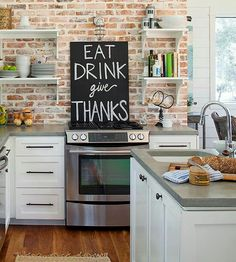 Exposed brick, white cabinets with cement counter tops, open shelves,  love the chalkboard sign over stove