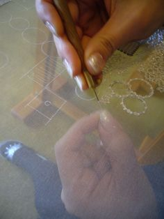 Close-up of worker doing luneville beading chez Lesage.