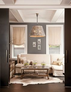 Grey and natural living room with drop cloth shades and slipcovers. Love the industrial coffee table and lamp. I so need some help with my living room.