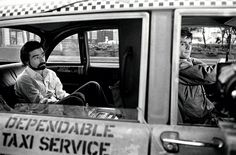 Martin Scorsese sitting in the backseat of Robert DeNiro's cab during the filming of Taxi Driver (1975)
