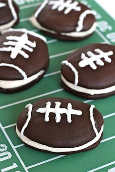 Football shaped chocolate cake-like cookies are sandwiched together with a fluffy marshmallow buttercream filling for a festive game time treat that's sure to be a winner!