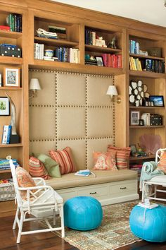 Our Best Living Room Wall Decor Ideas | Every inch of this living space is functionable with built-in open shelving for displaying a bookworm's collection and cozy upholstered bench for curling up with a new novel. #decorideas #homedecor #southernliving