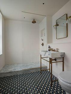 piso estampado e metais em bronze em banheiro