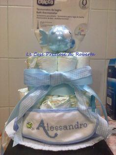 La torta è composta da 21 pannolini (taglia 4-9 kg), bavaglino ricamato a mano con il nome del bambino e Termometro per il bagnetto Chicco