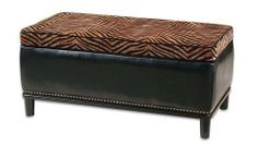 "Uttermost 42.5"" Inch Kiara Storage Bench Breathable, Cleanable Black Faux Leather by Utter. $521.40. Breathable, cleanable black faux leather with plush, golden brown and black woven top and black accent welt. Ebony stained, solid hardwood legs and base are accented with individually hammered, cast steel nails. Top lifts for storage using two reinforced"