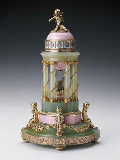 VAJÍČKO KOLONÁDA (1910) - Vajíčko od Fabergé jako hodiny, značící narození dlouho očekávaného nástupce trůnu Alexeje v roce 1904. Car Mikuláš II. jej daroval manželce Alexandře Fjodorovně na Velikonoce roku 1910. Na kupoli, která má světle růžový a bílý smalt, je Amor, kolem kterého je řada čísel z růžových briliantů. Čtyři zlacený andílci, umístěný na základně, představují dcery Romanova a spojený jsou květinovým věncem z různobarevného zlata. Dvě platinové holubice jsou uprostřed v kruhu.
