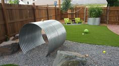 This is a dog-scape play area with artificial grass and culverts that serve as tunnel, perch area, and tomato planter.
